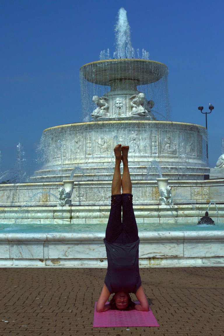 Woman doing yoga headstand in front of a fountain