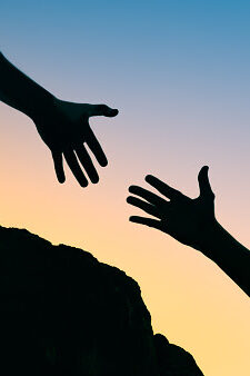 Persons hand reaching out to help another hand up a mountain cliff