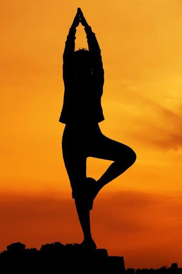 Girl doing tree yoga pose on rock during sunset